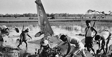 6 de junio de 1972: Milicianos junto a los restos de un avión estadounidense derribado por fuego de fusiles en los suburbios de Hanoi. Volaban a baja altura para evitar los radares, pero eran vulnerables a las armas ligeras cuando llegaban a bombardear, fundamentalmente las áreas industriales de la capital vietnamita. Foto: Doan Cong Tinh