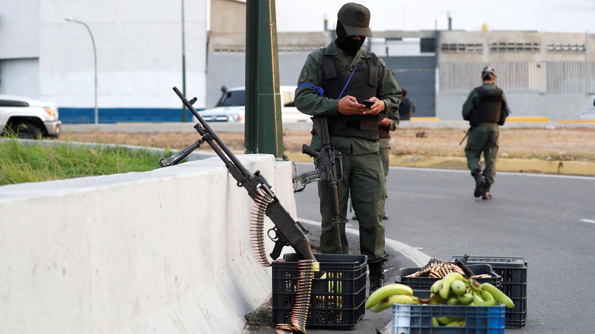 A military member uses his phone near the Generalisimo Francisco de Miranda Airbase in Caracas