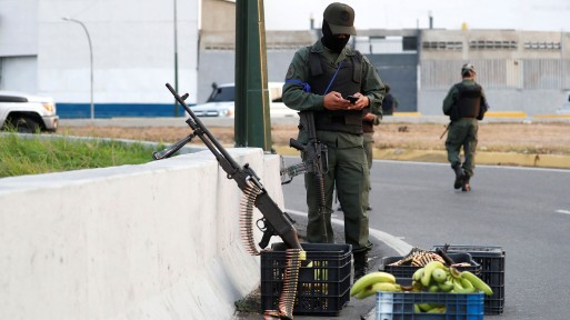 A military member uses his phone near the Generalisimo Francisco de Miranda Airbase in Caracas